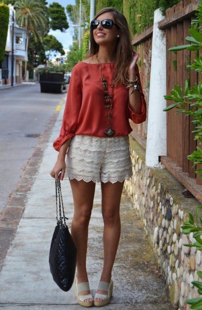 With red shirt, black bag and white sandals