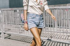 With silk blouse, denim shorts and small printed bag