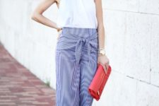 With striped pants, red clutch and sandals