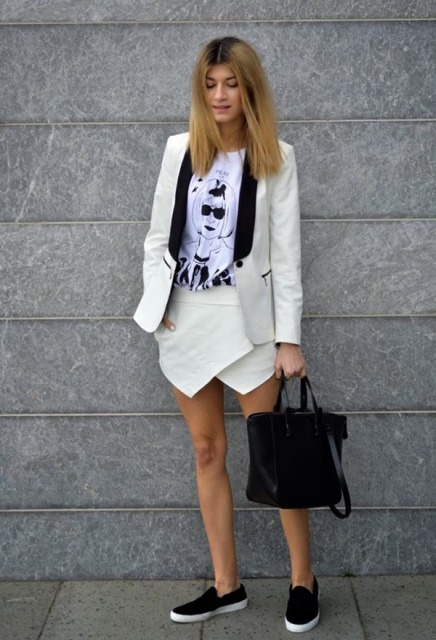 With t shirt, black and white blazer, slip on shoes and black bag