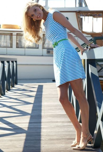 With white and blue striped dress and green belt