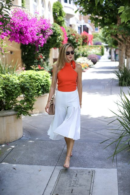 With white culottes and beige bag