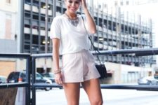 With white loose shirt, silver sandals and black bag
