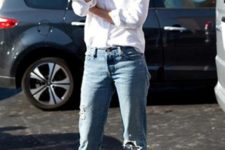 With white shirt and distressed jeans