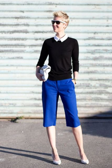 With white shirt, black sweatshirt, white clutch and pumps