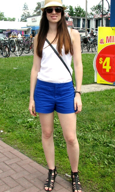 With white shirt, crossbody bag, lace up sandals and hat