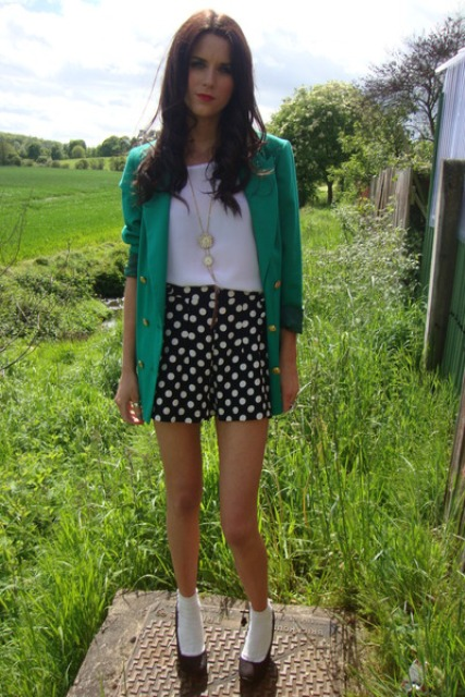 With white shirt, green blazer and black pumps