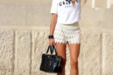 With white t-shirt, black bag and pumps