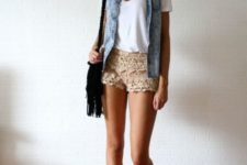 With white t-shirt, denim vest, sneakers and black bag
