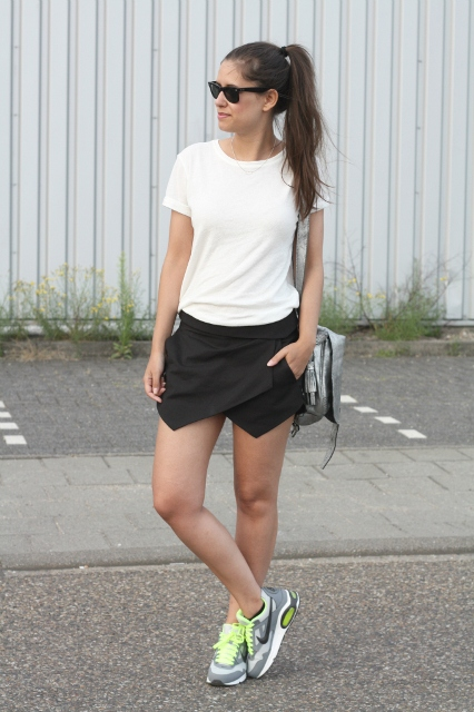 With white t shirt, sneakers and metallic bag