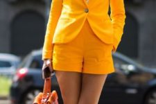 02 a bold yellow shorts suit with a striped shirt and tie and black pumps