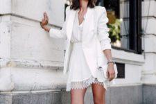 02 a white mini dress with a V neckline, a lace edge, a white blazer, crossbody bag and metallic shoes