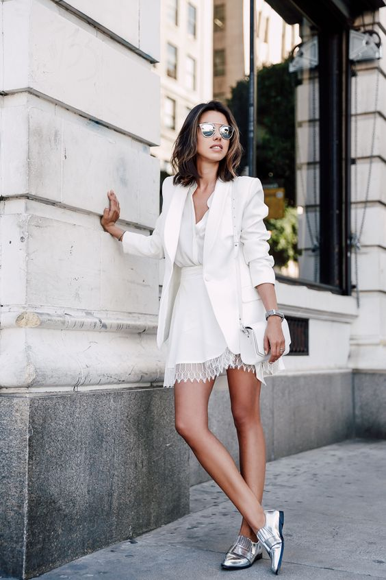 a white mini dress with a V neckline, a lace edge, a white blazer, crossbody bag and metallic shoes