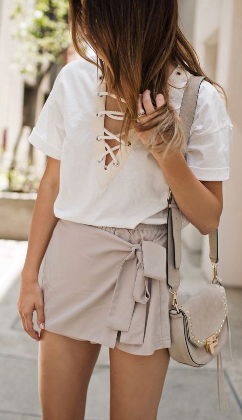 a blush wrap skirt with ties and white lace up shirt with short sleeves