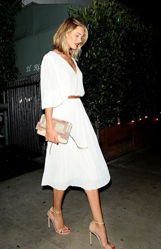 a flowy pleated white dress with wide half sleeves and a midi skirt, a clutch and nude ankle strap shoes