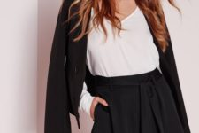04 a black shorts suit with a white V-neckline top and a black clutch