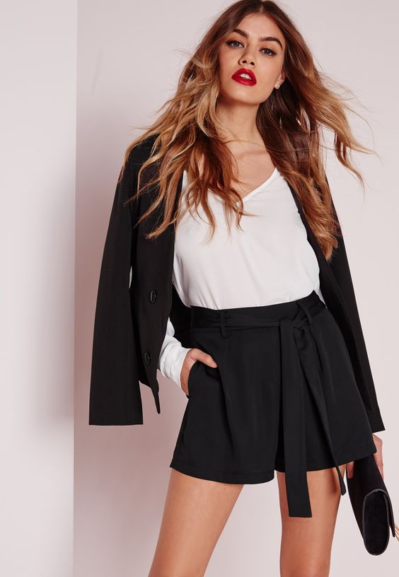 a black shorts suit with a white V-neckline top and a black clutch