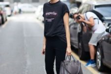 07 a black oversized tee, black pants, black leather boots and a grey bag