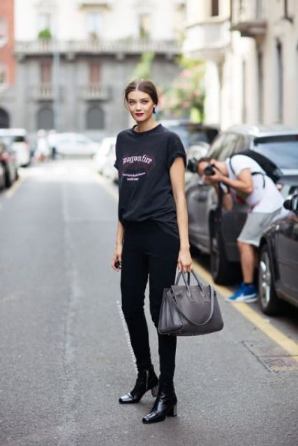 a black oversized tee, black pants, black leather boots and a grey bag