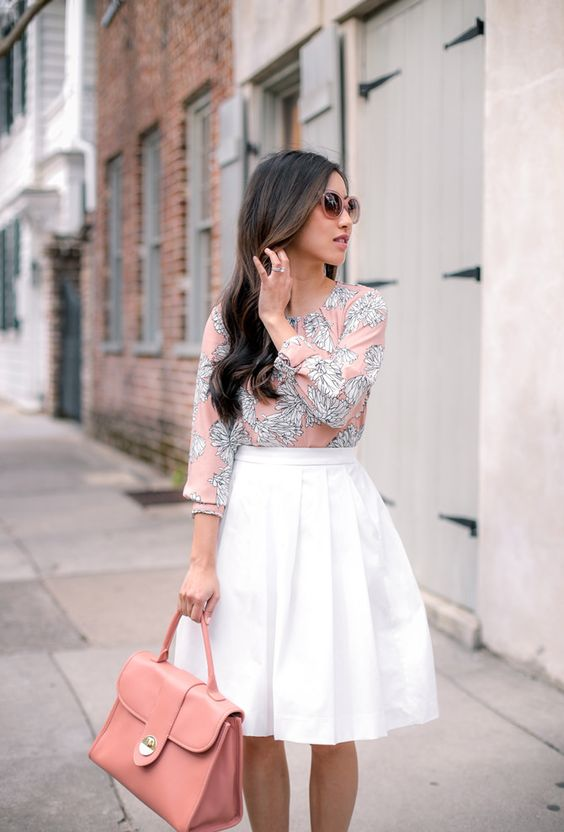 a white pleated midi skirt, a pink printed half sleeve shirt and a pink bag
