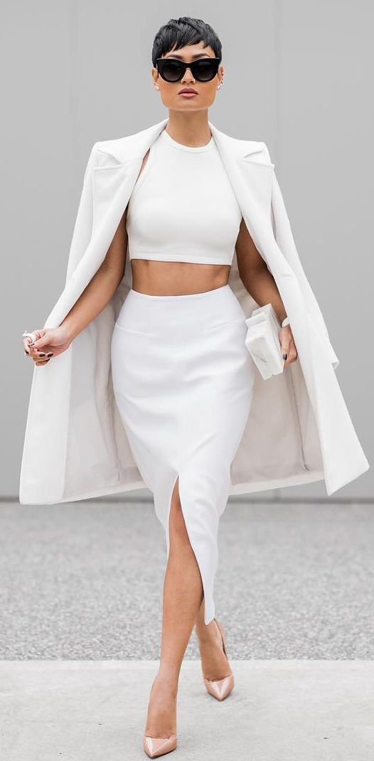 a white sleeveless crop top and a pencil skirt with a front slit, a white summer coat