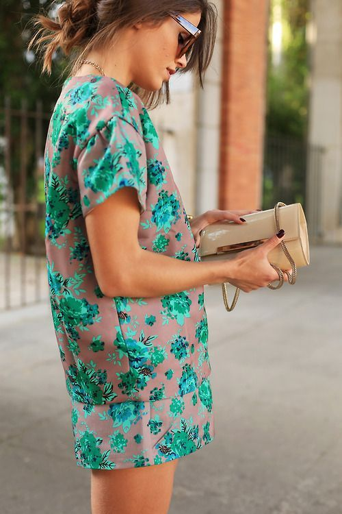 short chocolate dress with a bold emerald botanical print and a clutch
