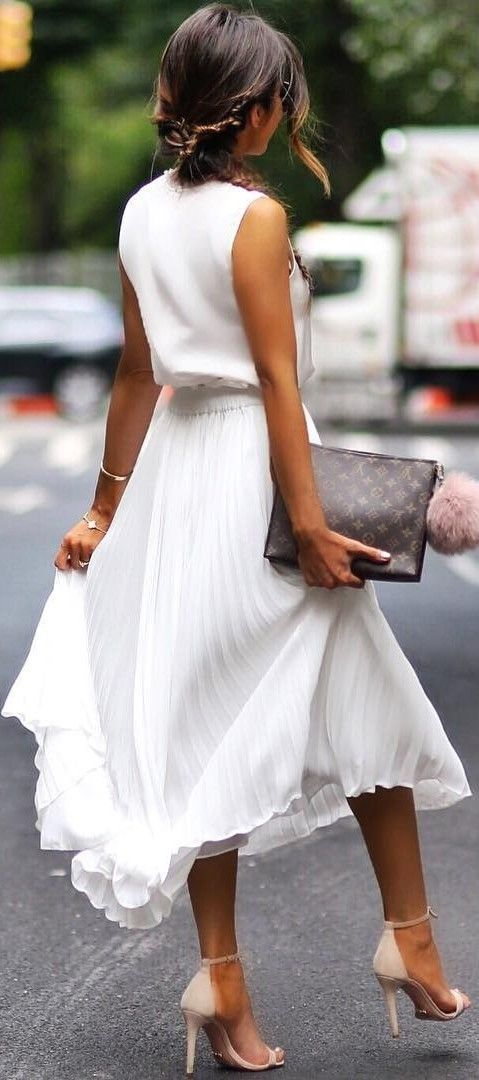 a white pleated midi skirt, a white sleeveless top, neutral heels and a clutch