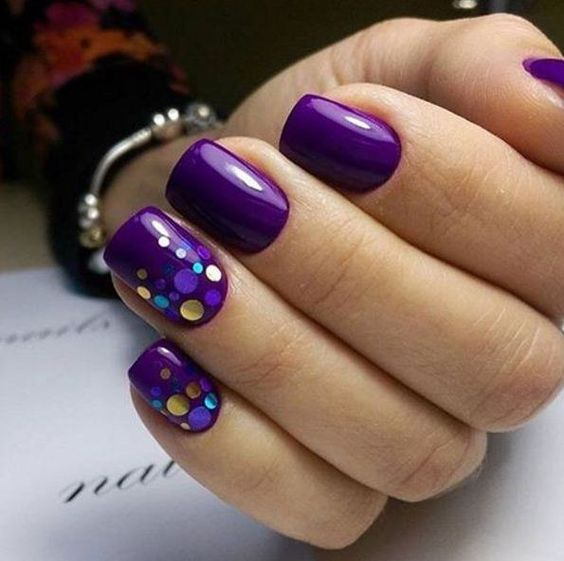 bold purple nails with two accent ones covered with sparkling polka dots