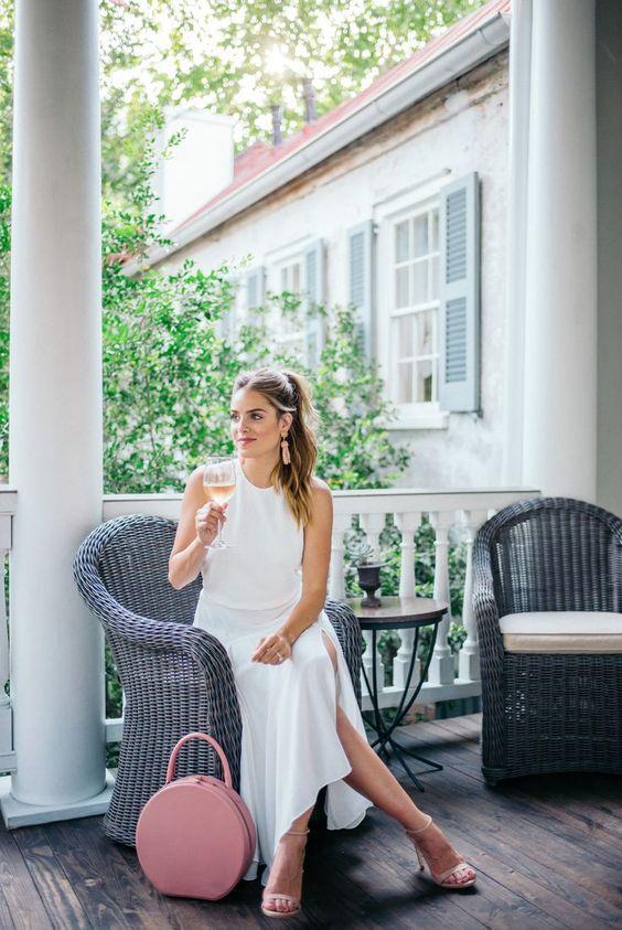 white halter neckline dress with a side slit, nude heels and a pink bag