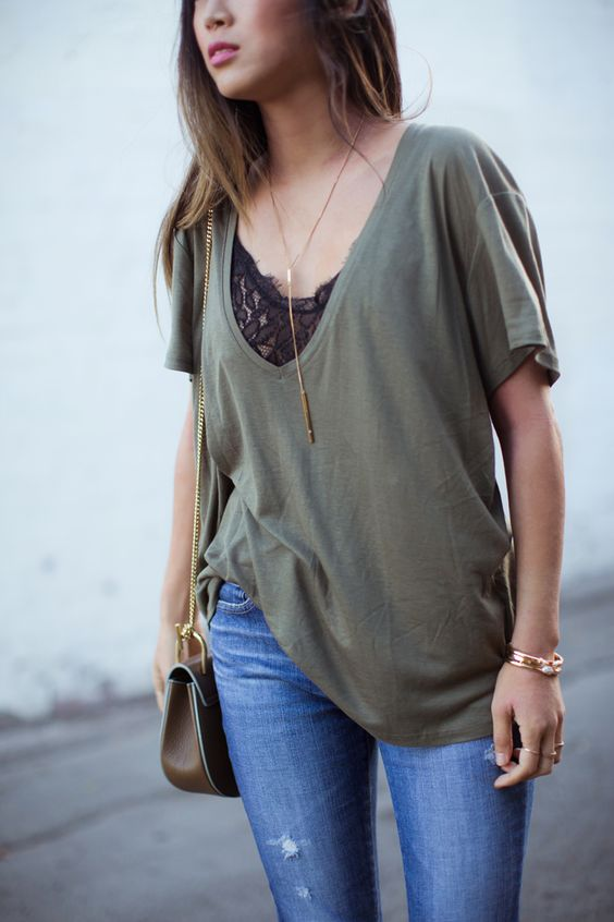 blue ripped jeans, a black lace top, an olive green oversized t-shirt