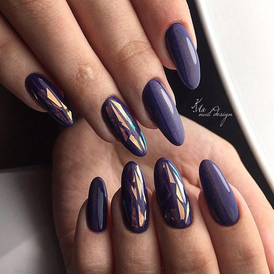 dark purple almond-shaped nails and accent ones with graphic designs