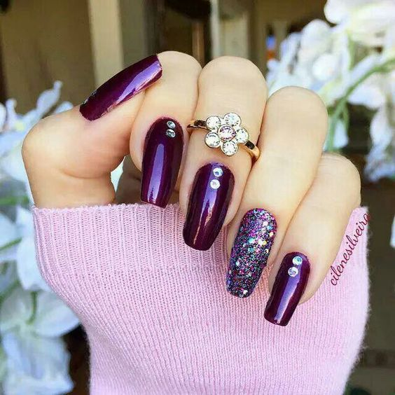 deep purple nails with an accent glitter nail and rhinestones