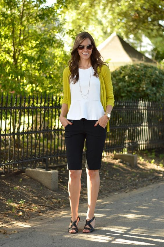 black bermuda shorts, a white ruche top, a mustard cardigan and black shoes