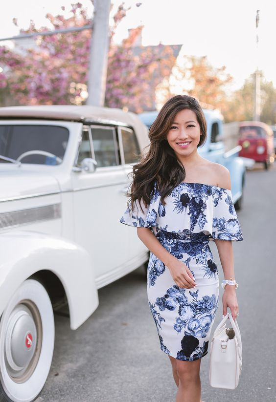 off the shoulder blue and white floral bodycon dress  and a white bag