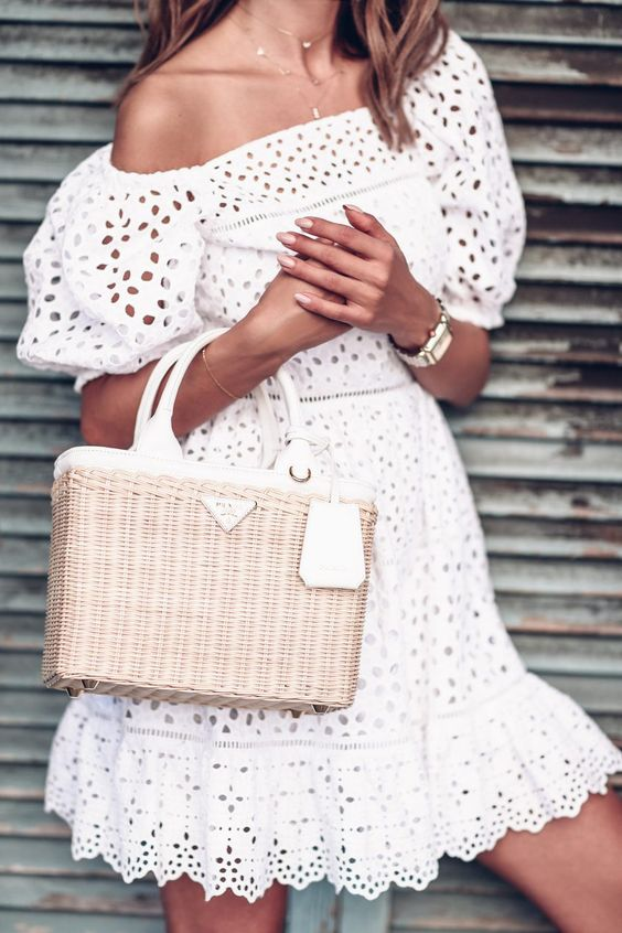 white off the shoulder perfeorated dress with half sleeves and a wicker Prada bag