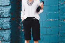13 black knee shorts, a white shirt, black ankle strap shoes and a statement necklace