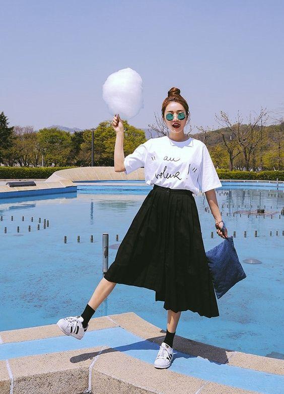 a black pleated skirt, a white printed tee and white chucks
