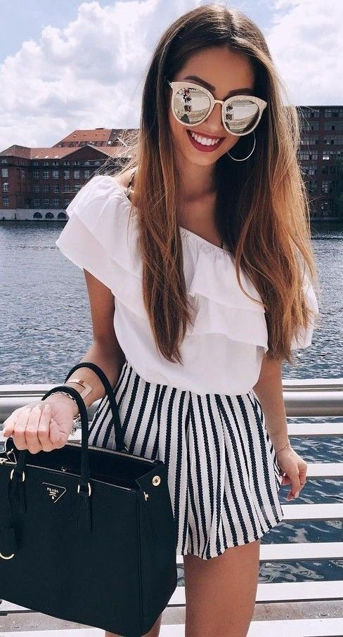 black and white striped shorts, a ruffled one shoulder top in white