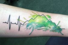 Mountain and heartbeat tattoo on the arm