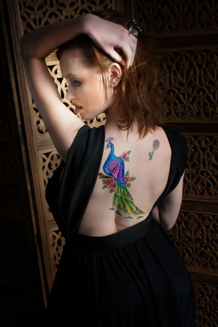Peacock with flowers tattoo on the back
