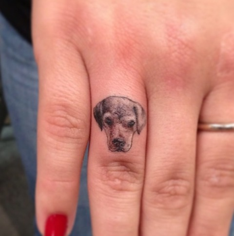 Tiny dog tattoo on the finger