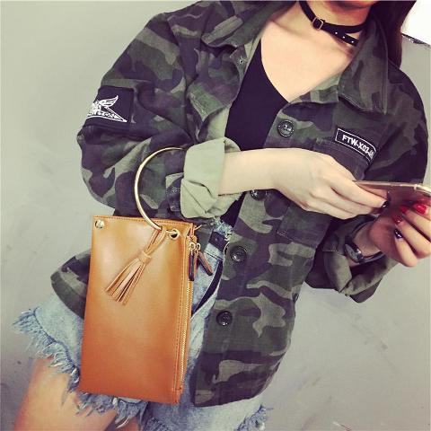 With army jacket, black top and fringe denim shorts