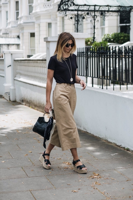 With black t shirt, beige culottes and platform sandals