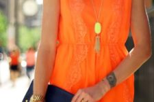 With golden necklace and navy blue clutch