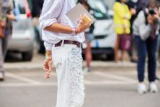With loose button down shirt, brown belt and white distressed jeans