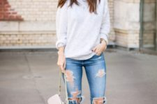 With loose sweatshirt, distressed jeans and small bag