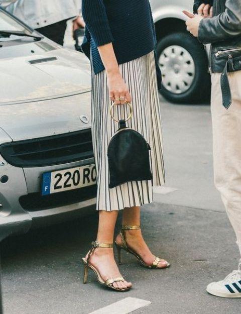 With navy blue shirt, pleated midi skirt and metallic heels