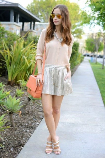 With pale pink blouse, orange bag and heels