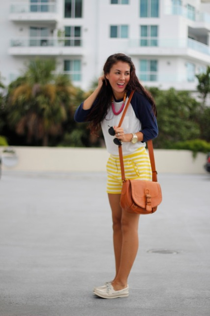 With white and navy blue shirt, yellow striped shorts and orange bag