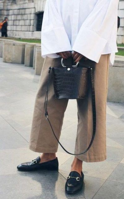 With white oversized shirt, beige culottes and black leather shoes